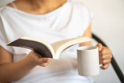 Closeup of woman hand holding and reading a book with holding white mug cup of hot coffee.