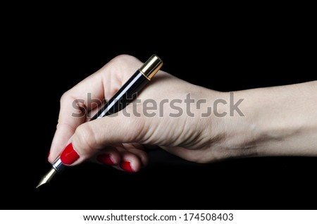 Closeup of woman hand holding pen on notebook isolated on black background