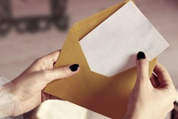 Closeup of Woman Hand Opening Envelope with Mockup Business Card or Blank Letter with Copyspace