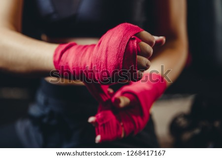Closeup of woman hands fist in sport protective bandages on black background, preparing for tough fight #1268417167