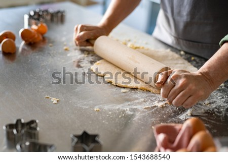 Closeup of woman hands holding rolling pin to flatten dough on kitchen counter. Old woman rolling dough for cookie on platform at home with ingredient around. Mature woman cooking christmas cookies. Stock photo ©