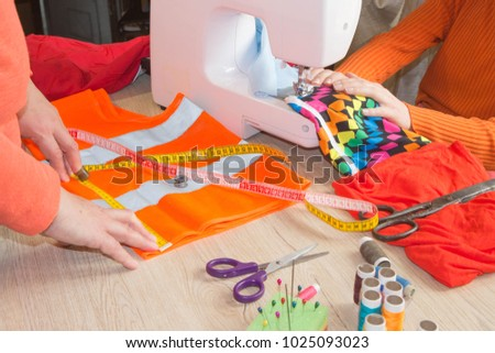 closeup of woman hands sewing yellow cloth outdoors. Hobby sewing fabric as a small business concept. Woman hand on sewing machine #1025093023
