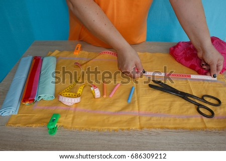 closeup of woman hands sewing yellow cloth outdoors. Woman's Hand Sewing Quilt #686309212