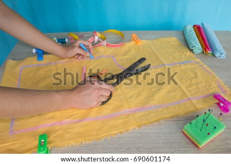 closeup of woman hands sewing yellow cloth outdoors. Woman's Hand Sewing Quilt #690601174