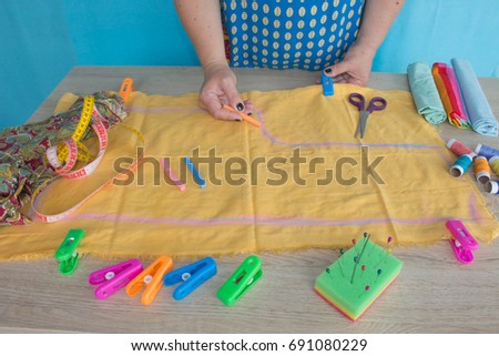closeup of woman hands sewing yellow cloth outdoors. Woman's Hand Sewing Quilt #691080229