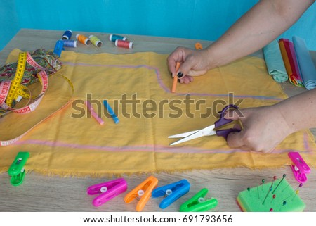 closeup of woman hands sewing yellow cloth outdoors. Woman's Hand Sewing Quilt #691793656