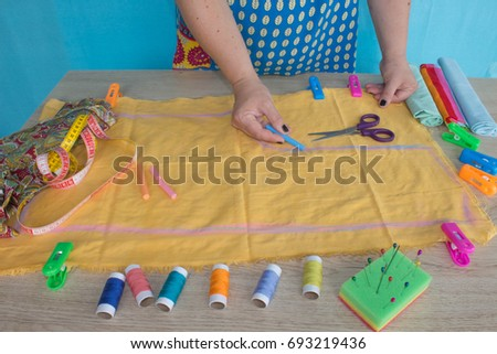 closeup of woman hands sewing yellow cloth outdoors. Woman's Hand Sewing Quilt #693219436