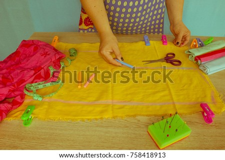 closeup of woman hands sewing yellow cloth outdoors. Woman's Hand Sewing Quilt #758418913