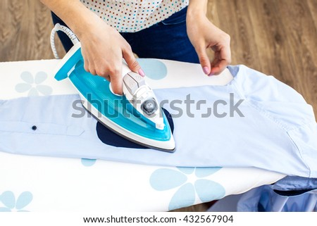 Closeup of woman ironing clothes on ironing board #432567904