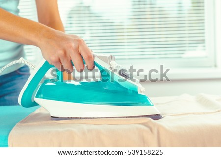 Closeup of woman ironing clothes on ironing board #539158225