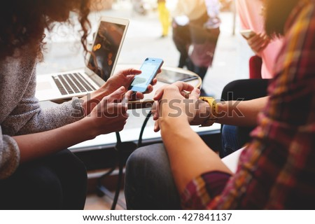 Closeup of woman is reading text message on mobile phone in network, while is sitting with laptop computer in co-working cafe. Group of friends are using gadgets during recreation time in coffee shop  #427841137