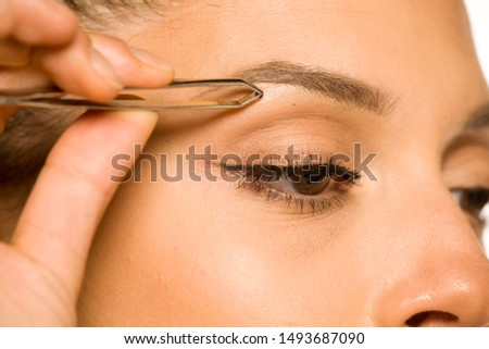 closeup of woman plucking her eyebrows with tweezers