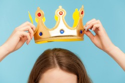 Closeup of woman putting on head golden crown, concept of awards ceremony, privileged status, superior position, self-motivation and big ambitions to achieve success. indoor studio shot, isolated
