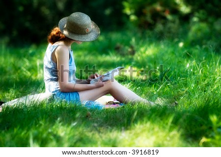 Closeup of woman reading book at the grass, side view