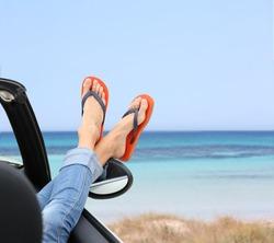 Closeup of woman's feet by convertible car window