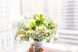 Closeup of woman's hand bride holding flower bouquet pink tone in front of bright sunny window in room of hotel, many flowers arrangement