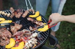 Closeup of woman's hand clamping grilled pork barbecue and vegetable on gridiron, roaster during family party.