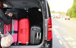 Closeup of woman's hand holding luggages, suitcases on back or rear side of black van car parking beside the street with natural background in bright sunny day.
