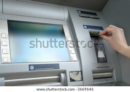 Closeup of woman's hand inserting e-card into ATM slot