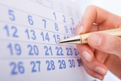 Closeup of woman's hand marking date 15 on calendar