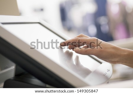 Closeup of woman's hand touching screen of cash register in store