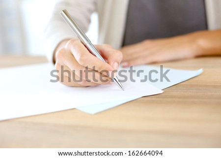 Closeup of woman\'s hand writing on paper