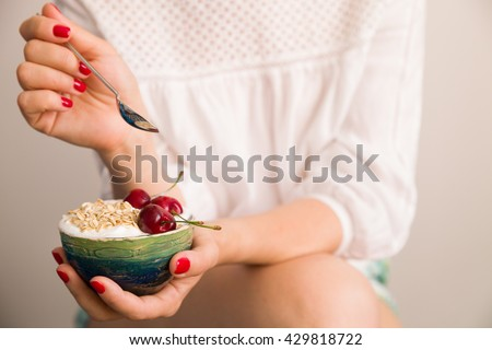 Closeup of woman\'s hands holding a cup with organic yogurt with oats and cherries. Homemade vanilla yogurt in girl\'s hands. Breakfast or snack. Healthy eating and lifestyle concept.