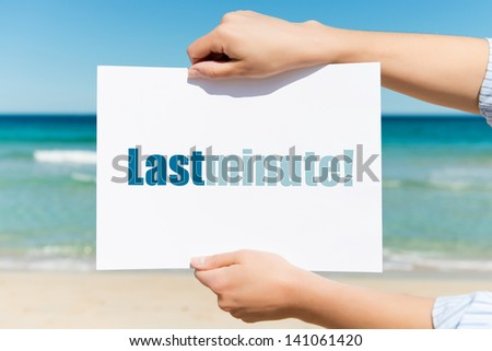 Closeup of woman\'s hands holding placard with Last Minute sign on beach
