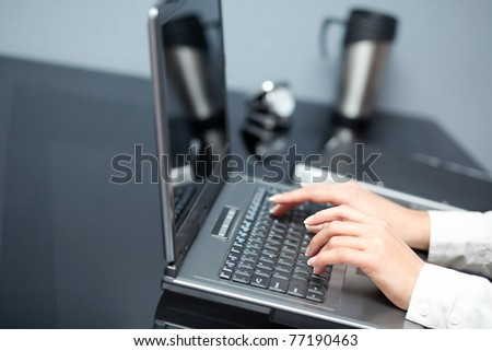 Closeup of woman's hands touching notebook (laptop) keys during work. In office interior.
