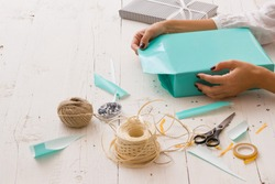 Closeup of woman's hands with gift ribbon, twine, tape and present wrapped in turquoise gift paper on white wooden background. Christmas, birthday or any other celebration preparations.