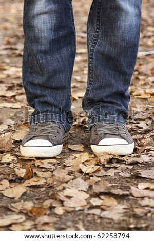 closeup of woman's legs in jeans and sneakers, outdoor in autumn park