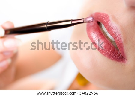 Closeup of woman's lips and  a brush with lipstick