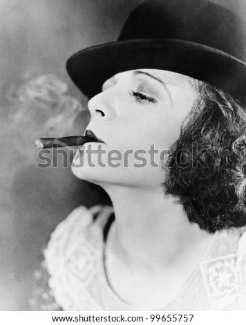 Closeup of woman smoking cigar - stock photo