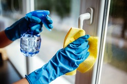 Closeup of woman wearing blue rubber gloves cleaning the window handle with microfiber rag and sanitizing spray during coronavirus pandemic quarantine. Health care and adaptation concept.