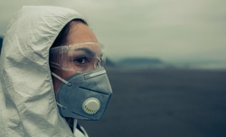 Closeup of woman with bacteriological protection suit on the beach
