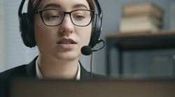 Closeup of woman working in callcenter consulting client online, employee working in customer service support, head shot