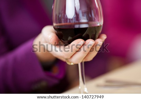 Closeup of women's hand holding wine glass at restaurant table