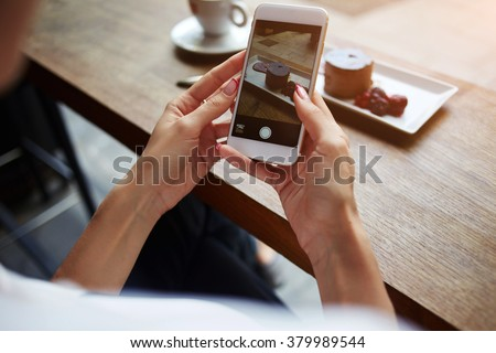 Closeup of women\'s hands making photo of sweet dessert on mobile phone while sitting in comfortable restaurant, female taking pictures with cell phone camera of delicious pastry during rest in cafe