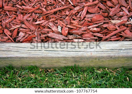 Closeup of wood chip on garden with wooden border and green grass - stock photo