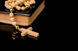 Closeup of wooden Christian cross on bible and prayer beads on b
