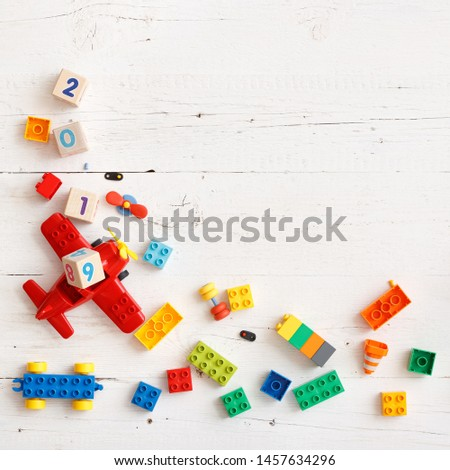 Closeup of wooden cubes with numbers 2018, 2019 year. Top view on children's educational toys, multi-colored cubes, bricks and other details on a white wooden background. #1457634296