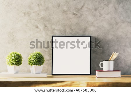 Closeup of wooden table with blank frame, two flowerpots, iron mug with pencils and book on concrete background. Mock up