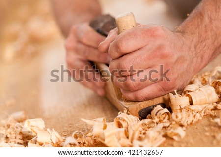 closeup of woodworker\'s hands shaving with a plane in a joinery workshop