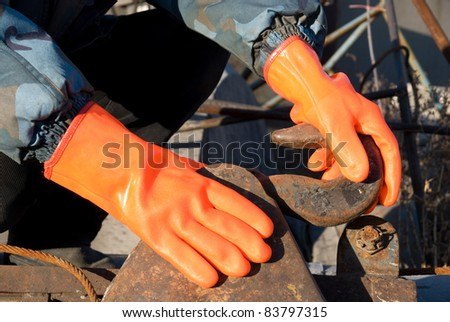 Closeup of worker man at orange gloves