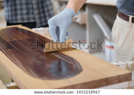 Closeup of workers hand covering wooden plank with finishing protective cover for wood, carpentry furniture woodworking production #1415218967