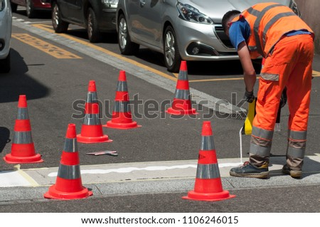 closeup of workers painting a white pedestrian crosswalk at a street with orange cones for safety #1106246015