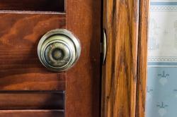Closeup of worn vintage brass doorknob on louvered wood door