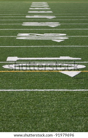 Closeup of yard lines from scrimmage line on football, soccer field