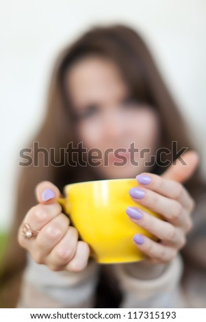 Closeup of yellow cup in woman hands