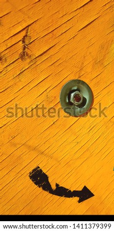 closeup of yellow painted wooden cable drum with single unwind direction arrow #1411379399